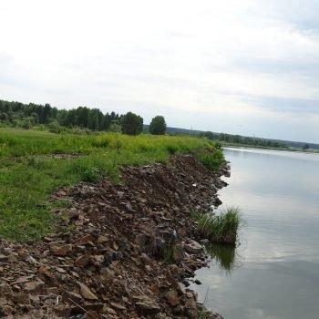 Крепление верхового откоса грунтовой плотины каменной наброской гидротехнического сооружения Некрасовского (верхнего) водохранилища